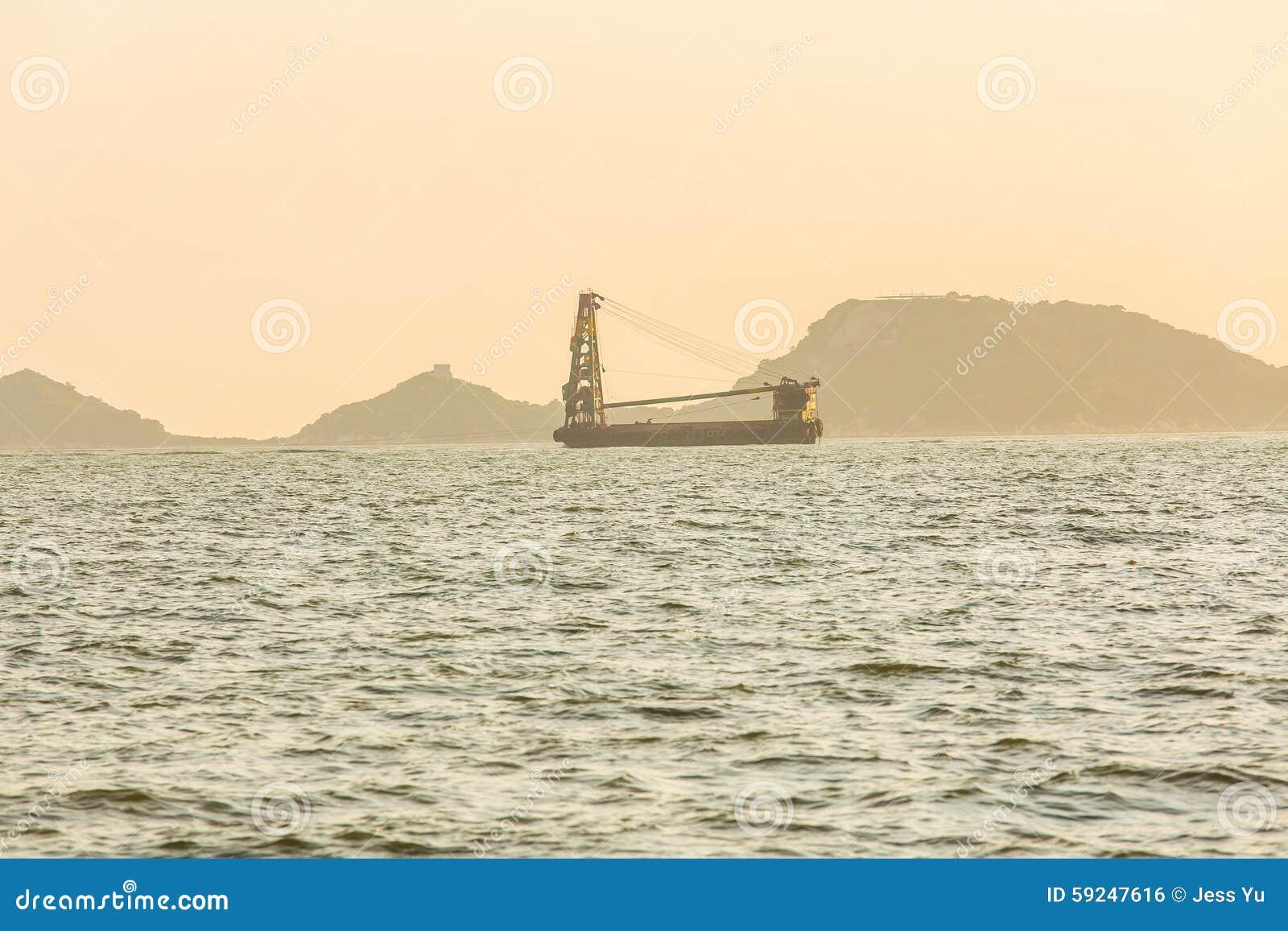 Barco de navegación en la puesta del sol en el océano