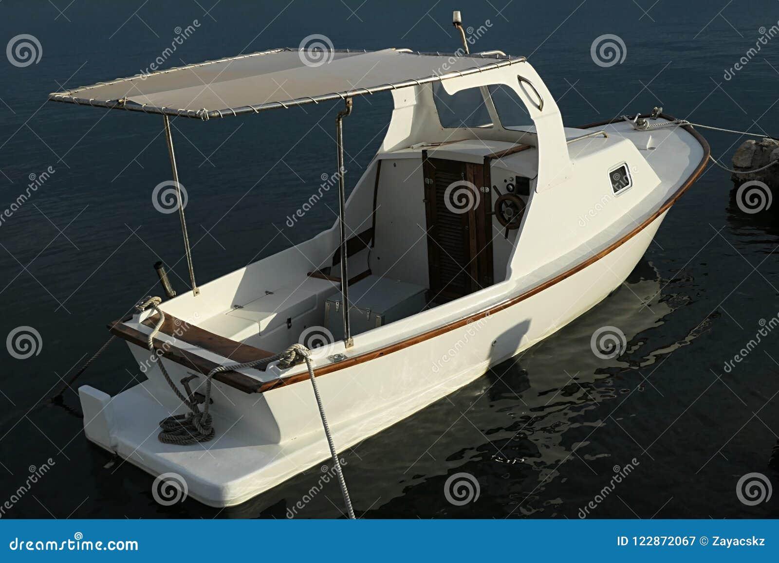 Barco de pesca branco pequeno do motor com leme de madeira, cabine pequena simples na parte dianteira