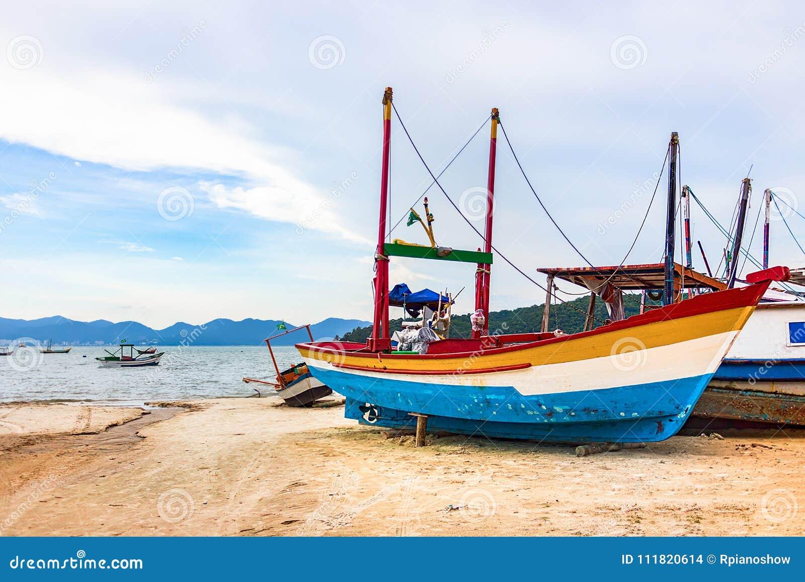 Barco de pesca de madeira colorido na praia em Porto Belo