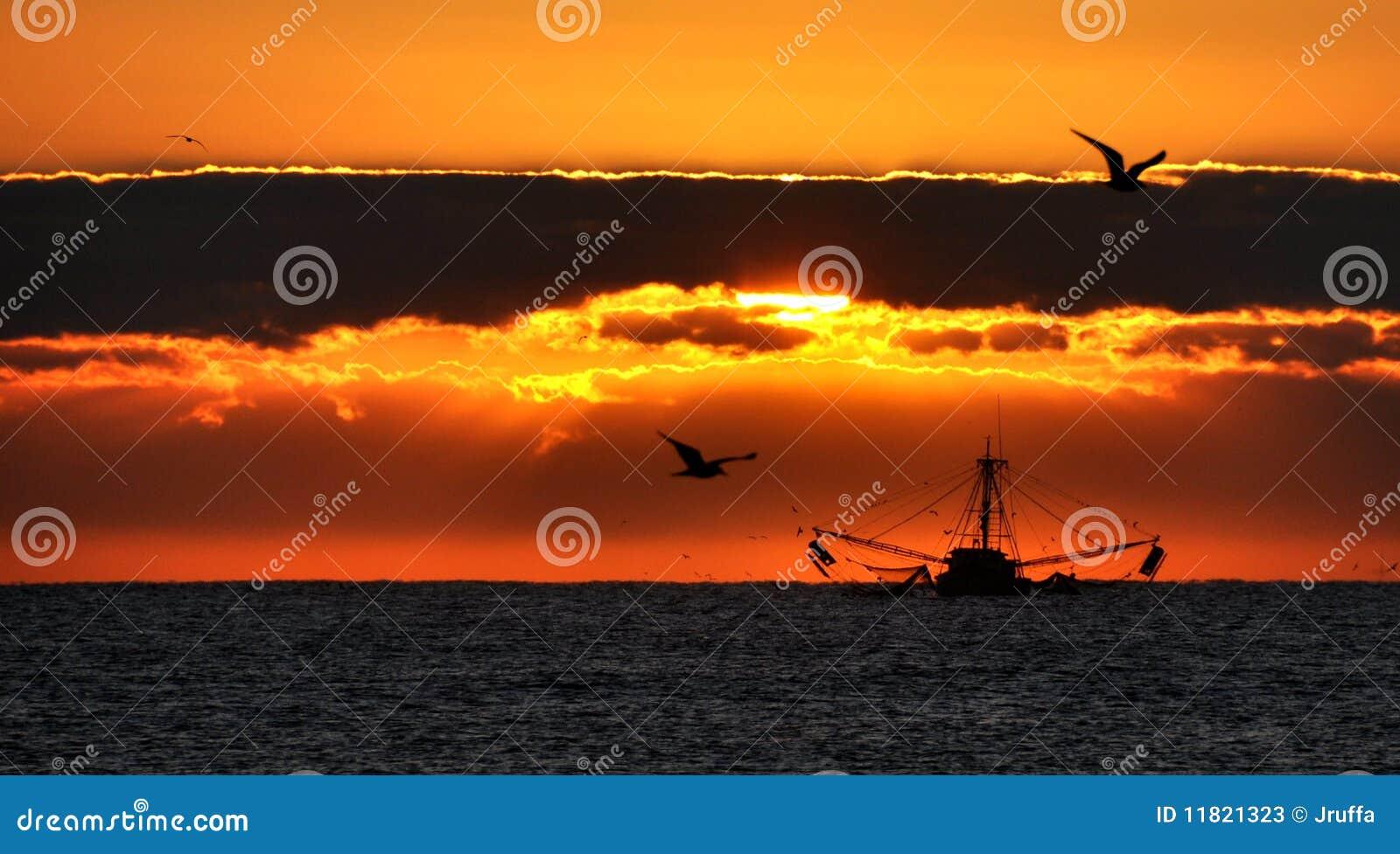 Barco de pesca no nascer do sol