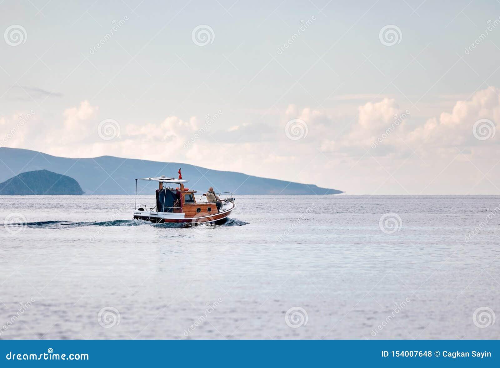 Barco de pesca que leva uma navigação de dois pescadores sobre o mar calmo no tempo de inverno em Gumusluk, Bodrum, Turquia