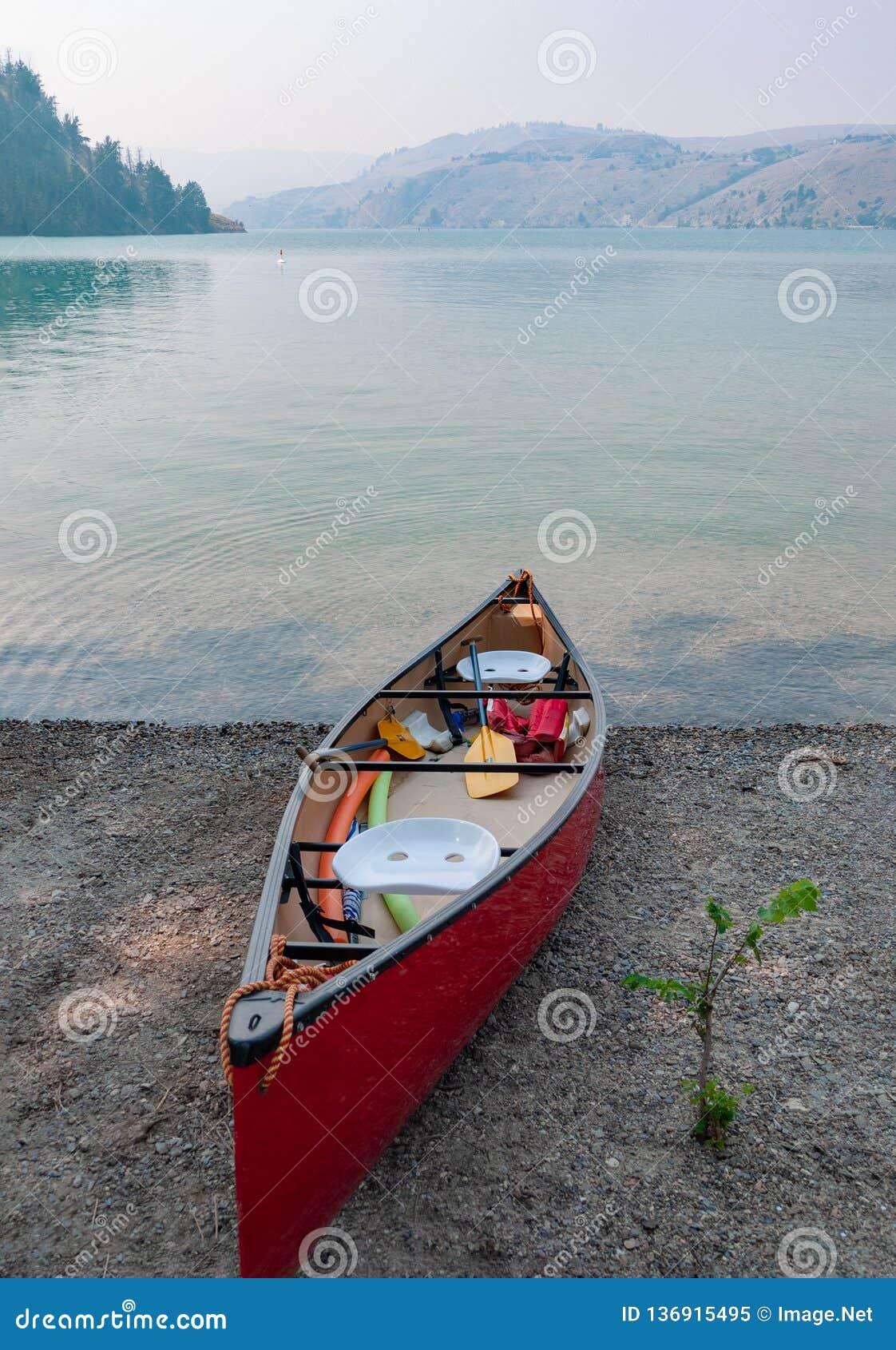 Barco de pouco peso vermelho da canoa em uma costa do lago Kalamalka