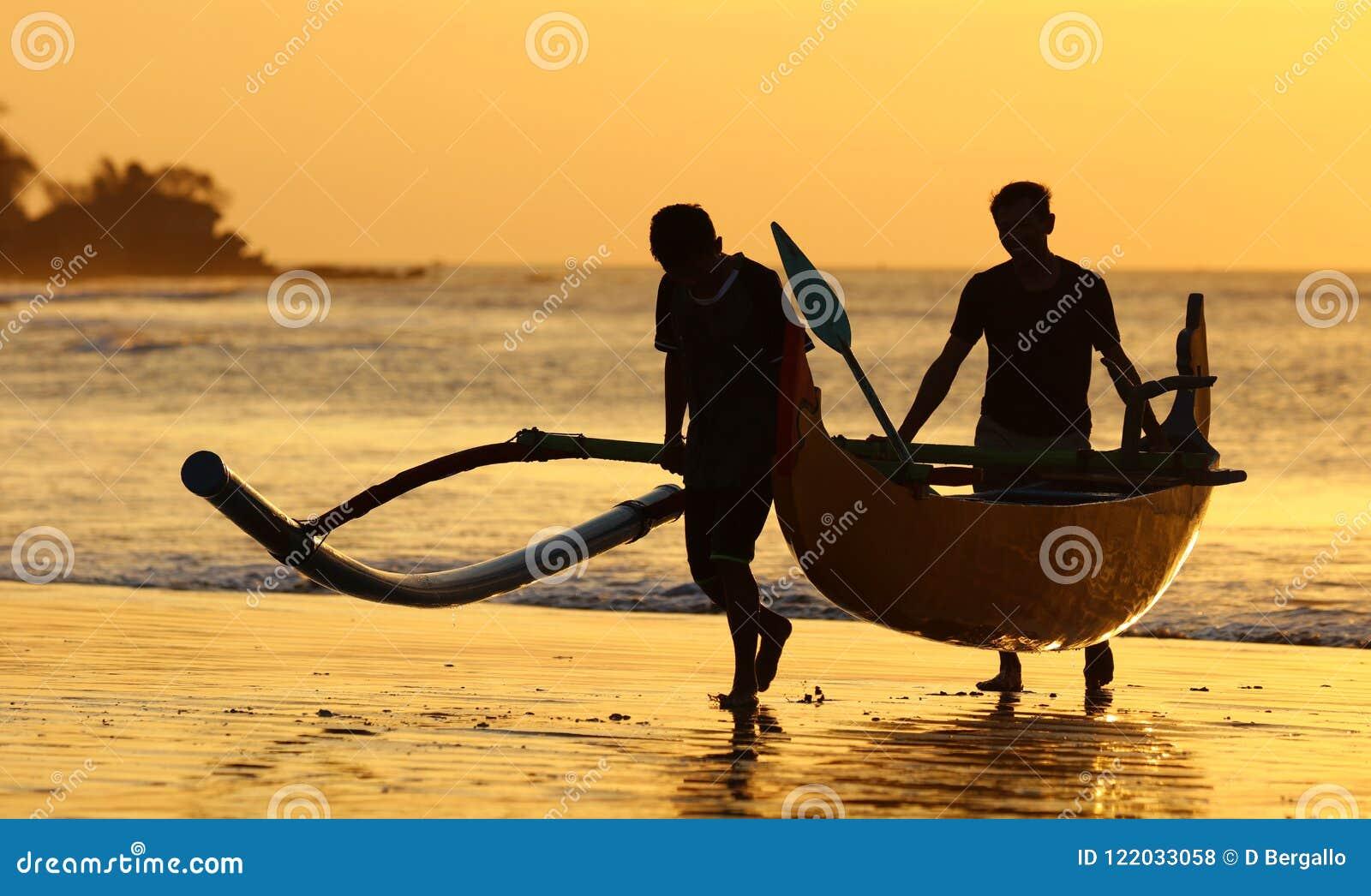 Barco del pescador con dos pescadores en Bali, Indonesia durante puesta del sol en la playa