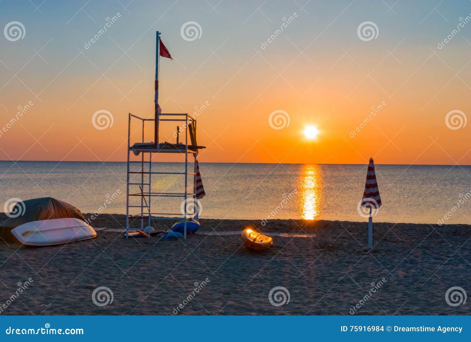 Barco do parasol do nascer do sol do por do sol da praia da torre da salva-vidas
