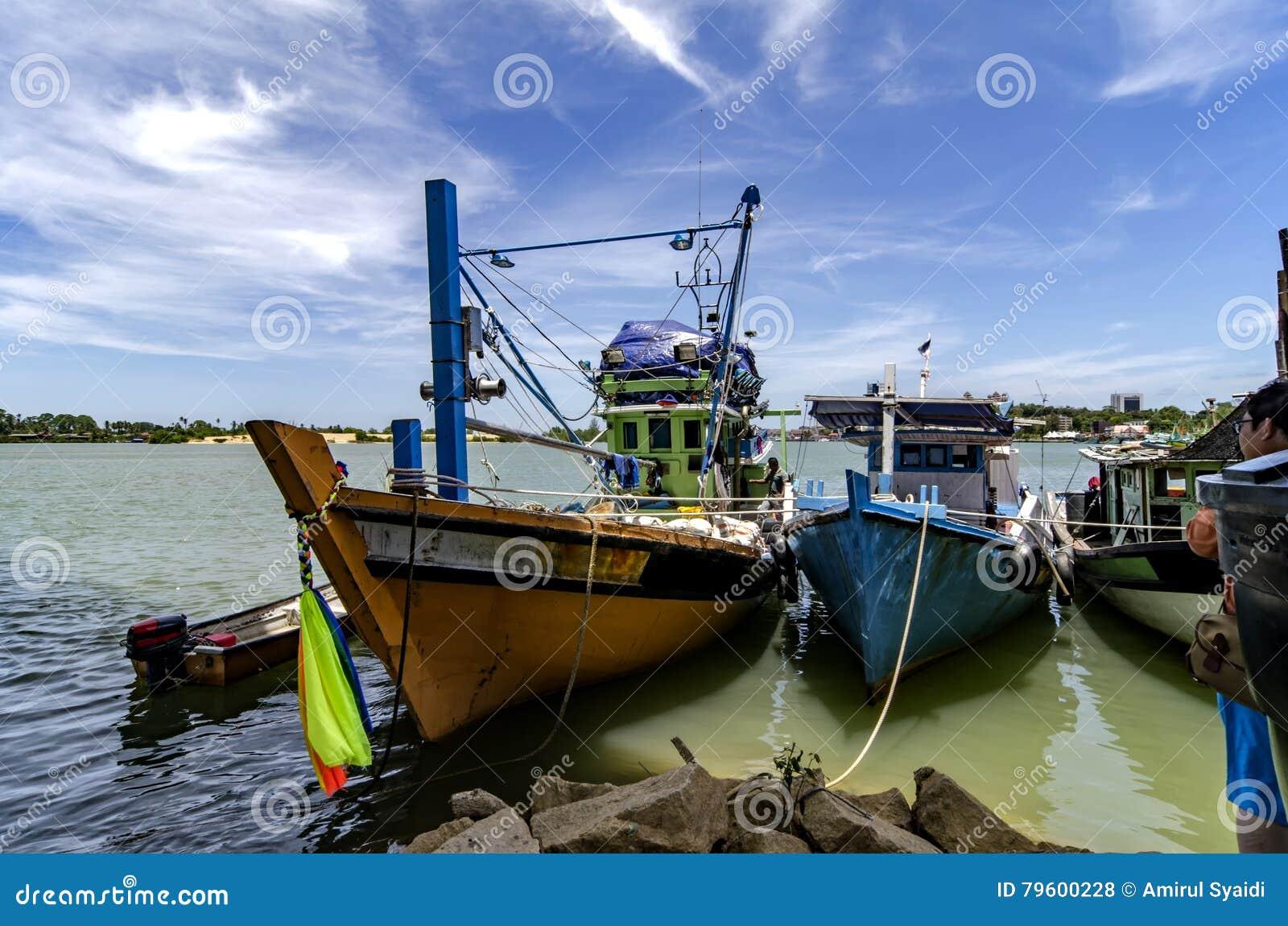Barco do pescador ancorado sobre o céu nebuloso e azul no dia ensolarado