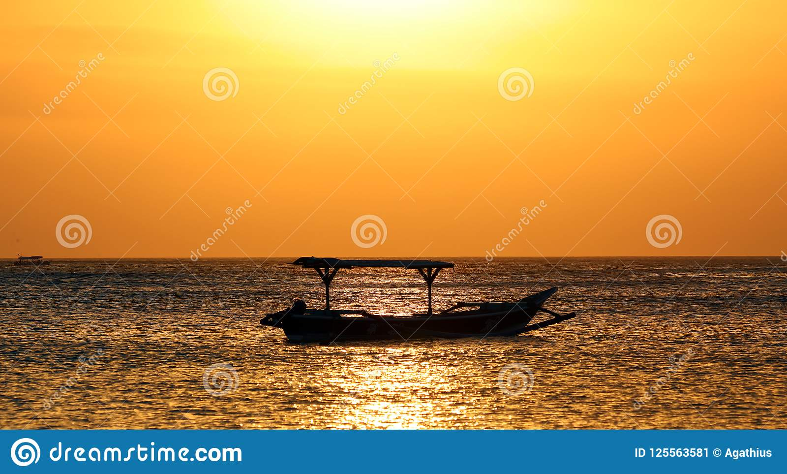 Barco do pescador em Bali, Indonésia durante o por do sol dourado Oceano e céu que olham como o ouro