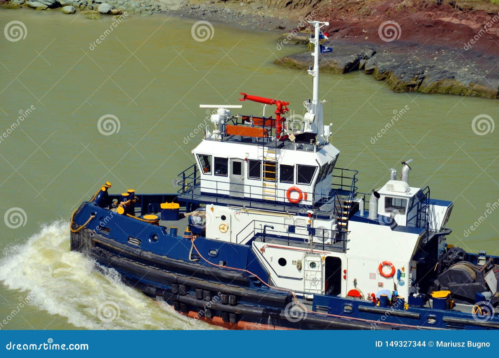 Barco do reboque do canal do Panamá que ajuda aos navios de carga
