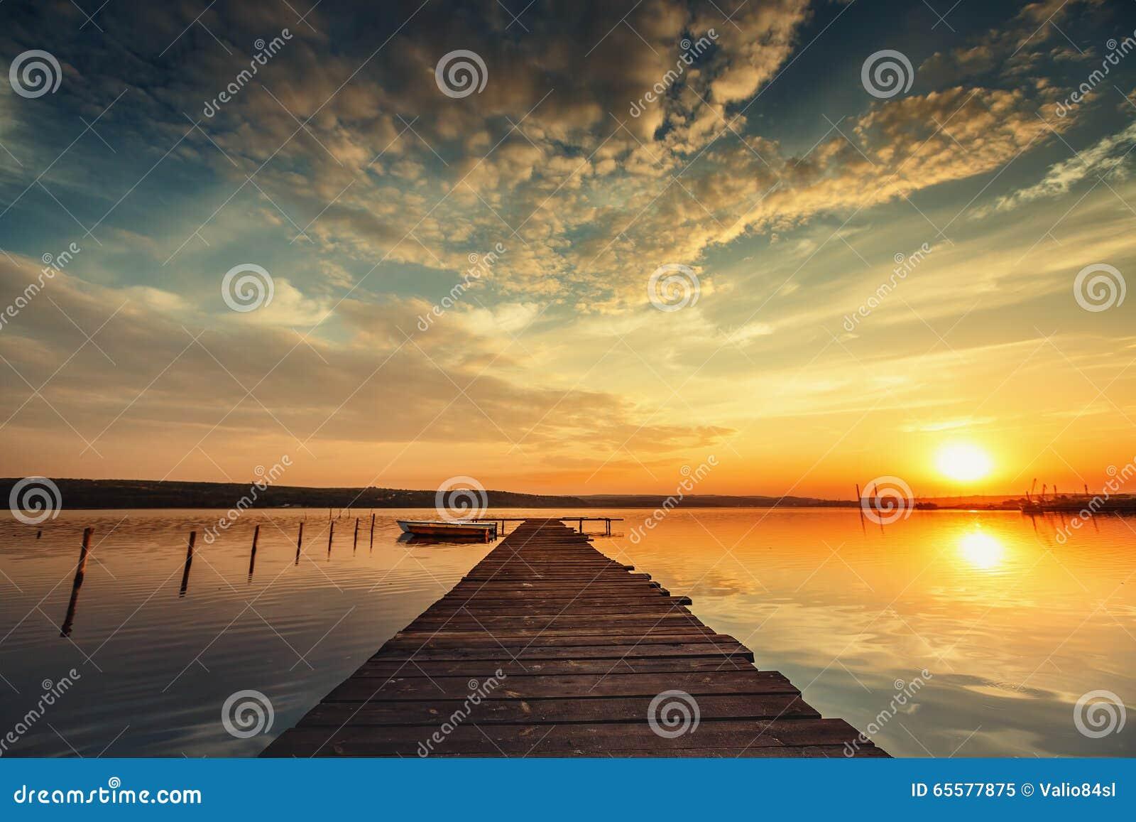 Barco e molhe no lago com uma reflexão na água no por do sol