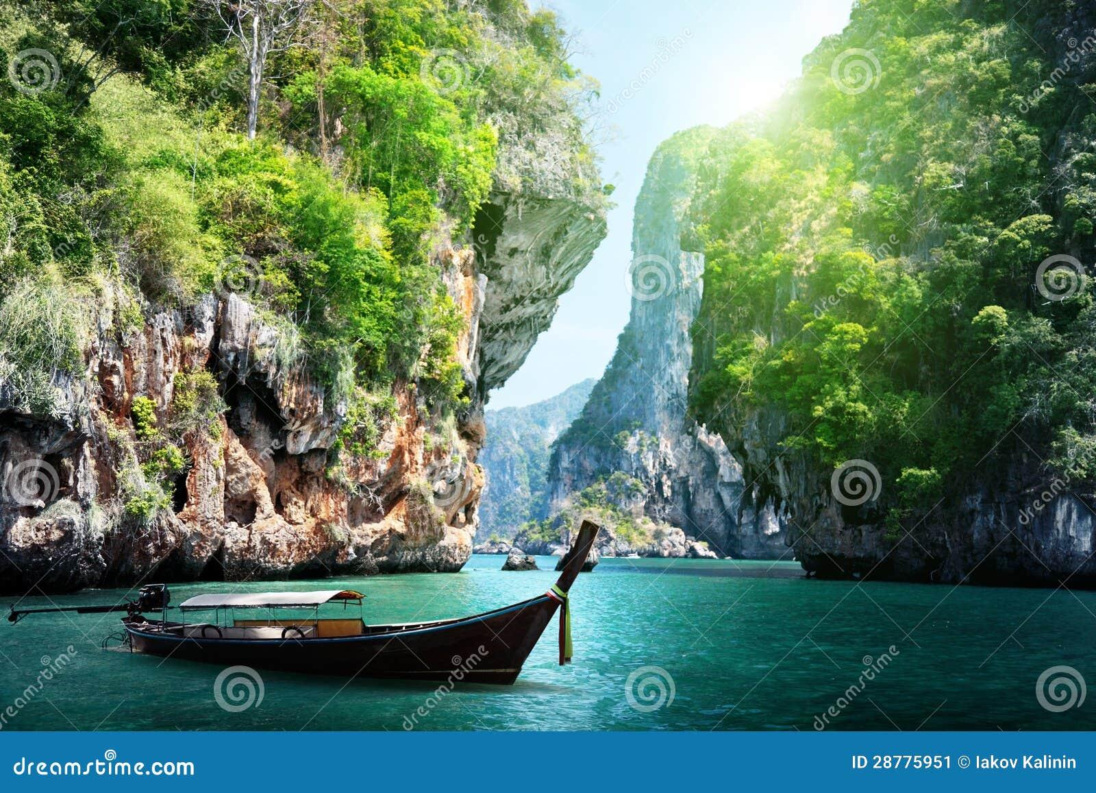 Barco e rochas longos na praia railay em Tailândia
