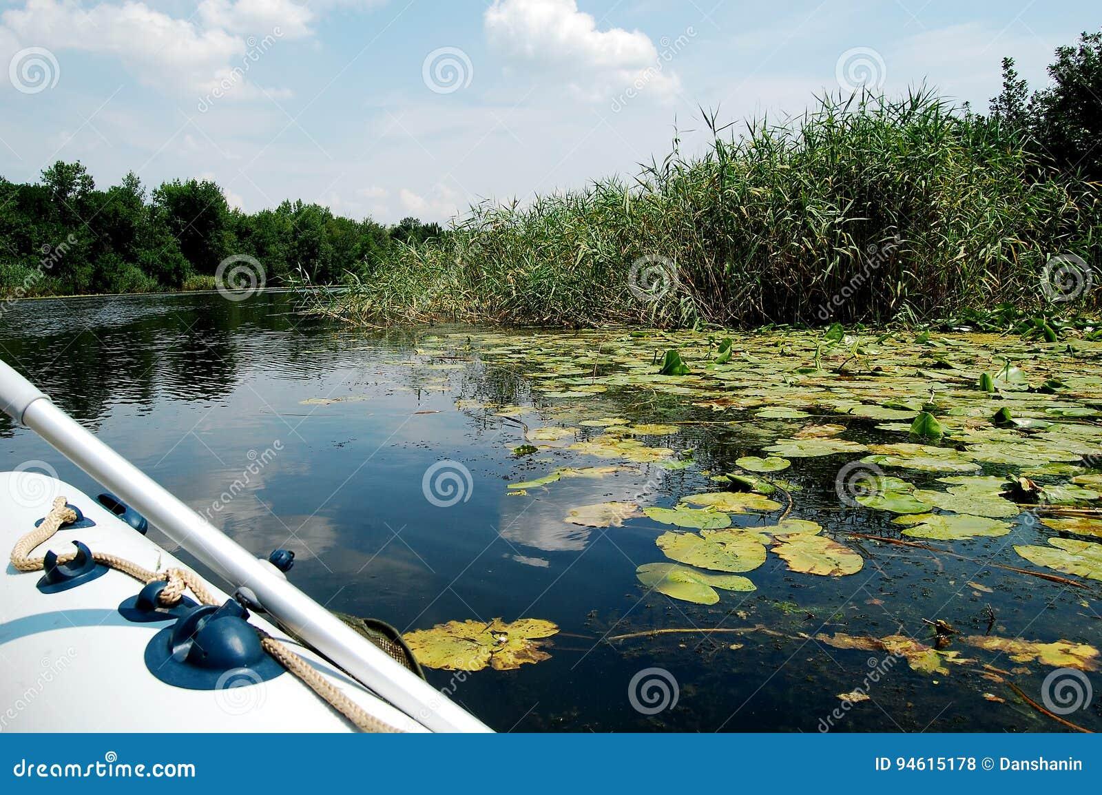 Barco inflável em um rio estreito no meio-dia