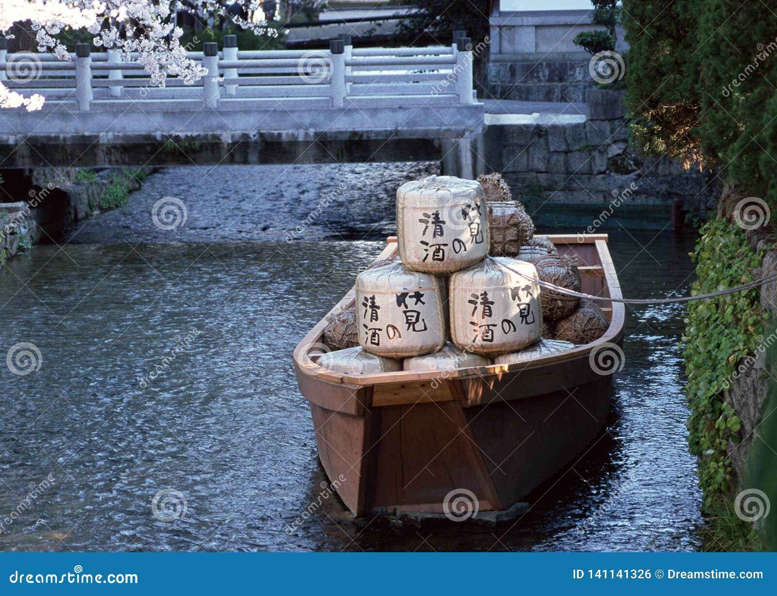 Barco japonés con las mercancías en un río atado al banco con un fondo de la cuerda