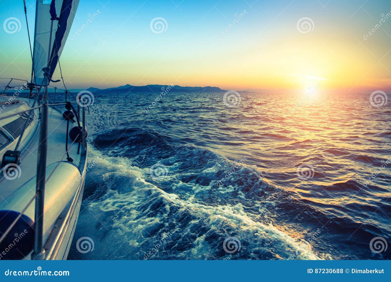 Barco na regata da navigação durante o por do sol nave