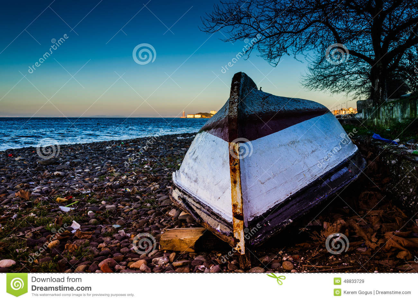 Barco a remos invertido dos pescadores na costa do por do sol