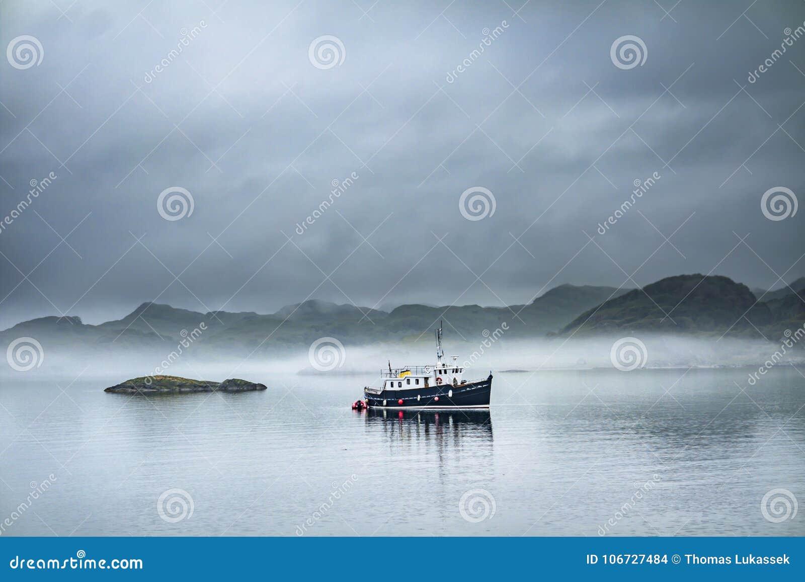 Barco sozinho que conduz completamente no mar nevoento nas montanhas escocesas