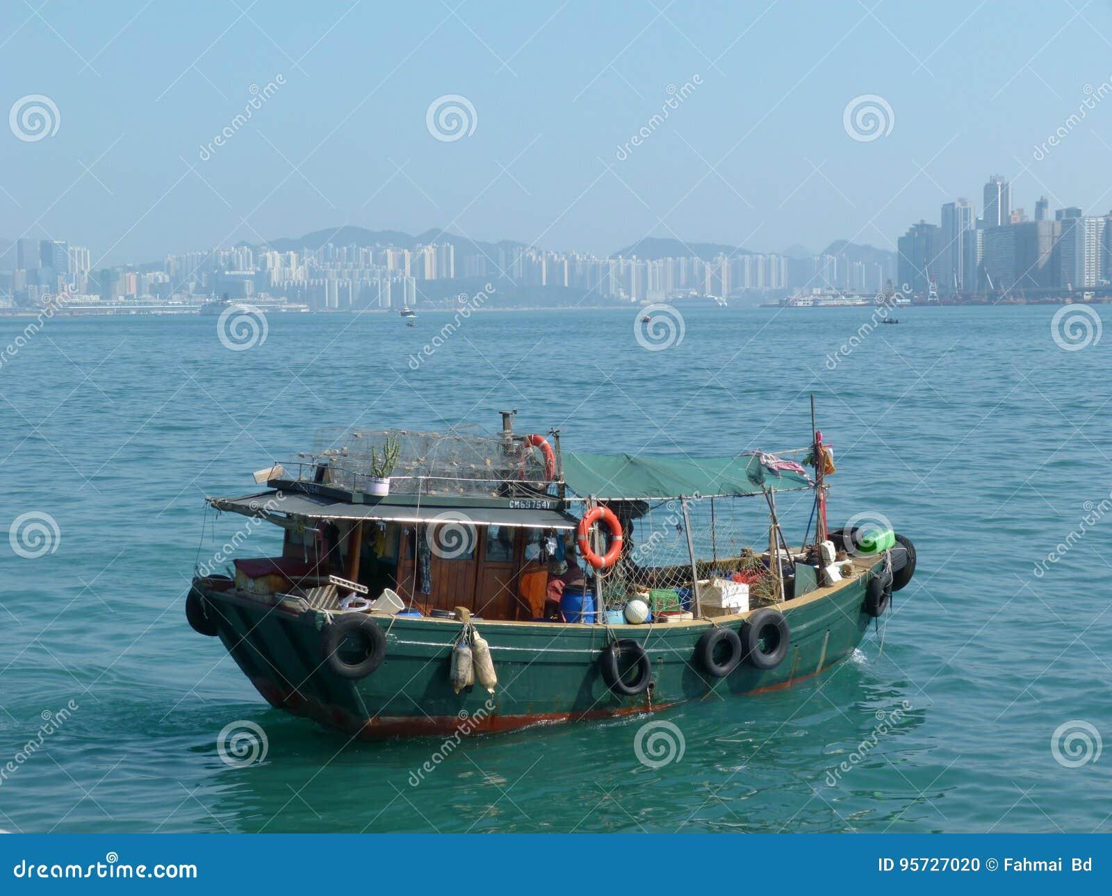 Barco velho do pescador com terra da parte traseira da construção alta