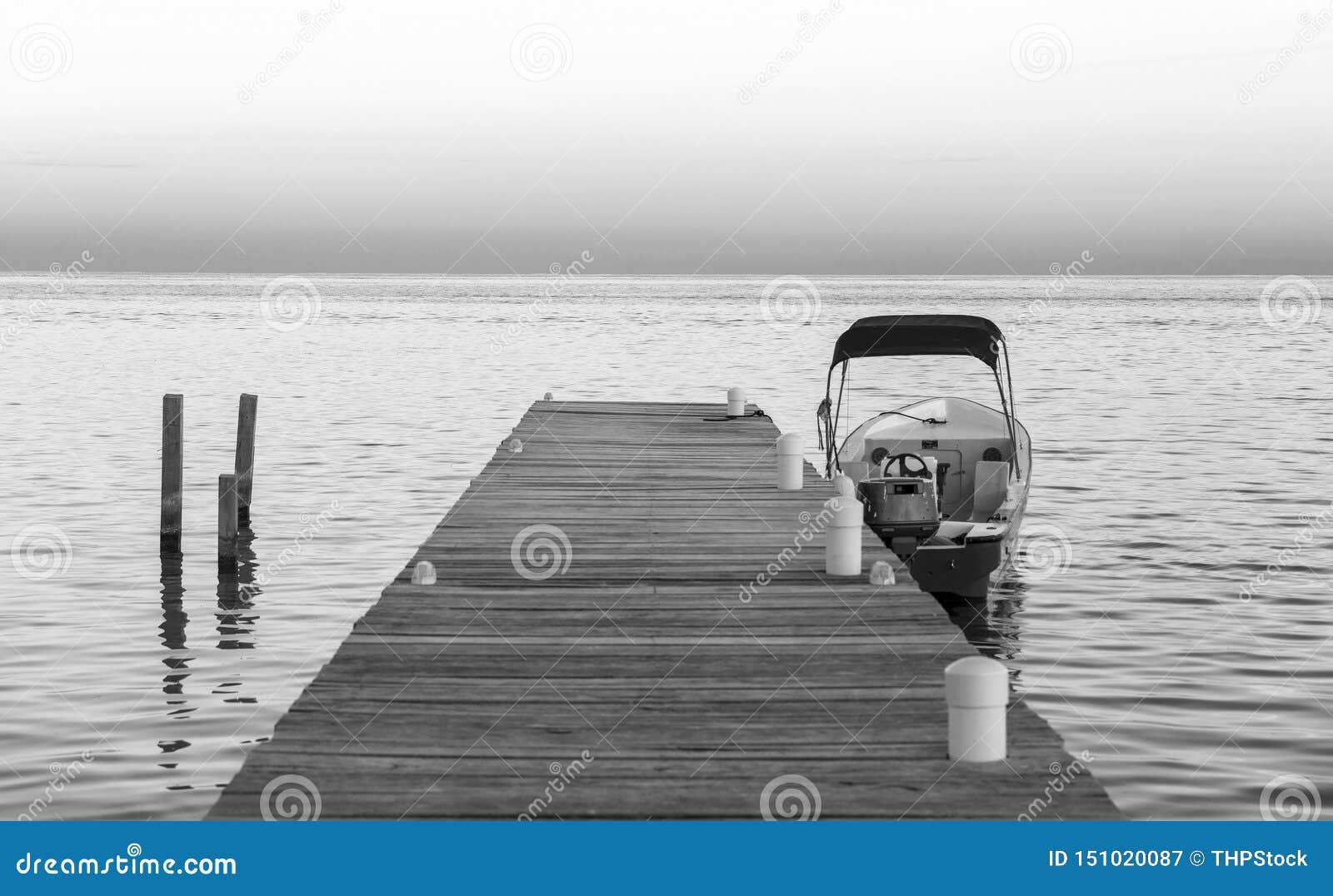 Barco y embarcadero en la salida del sol blanco y negro