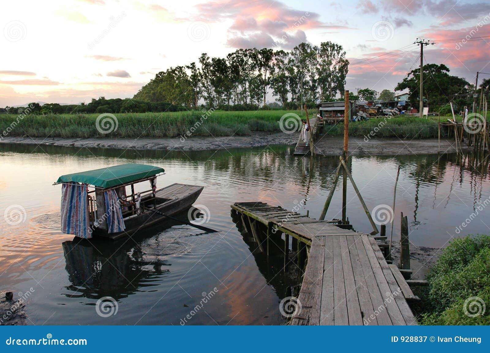 Barco y río en puesta del sol