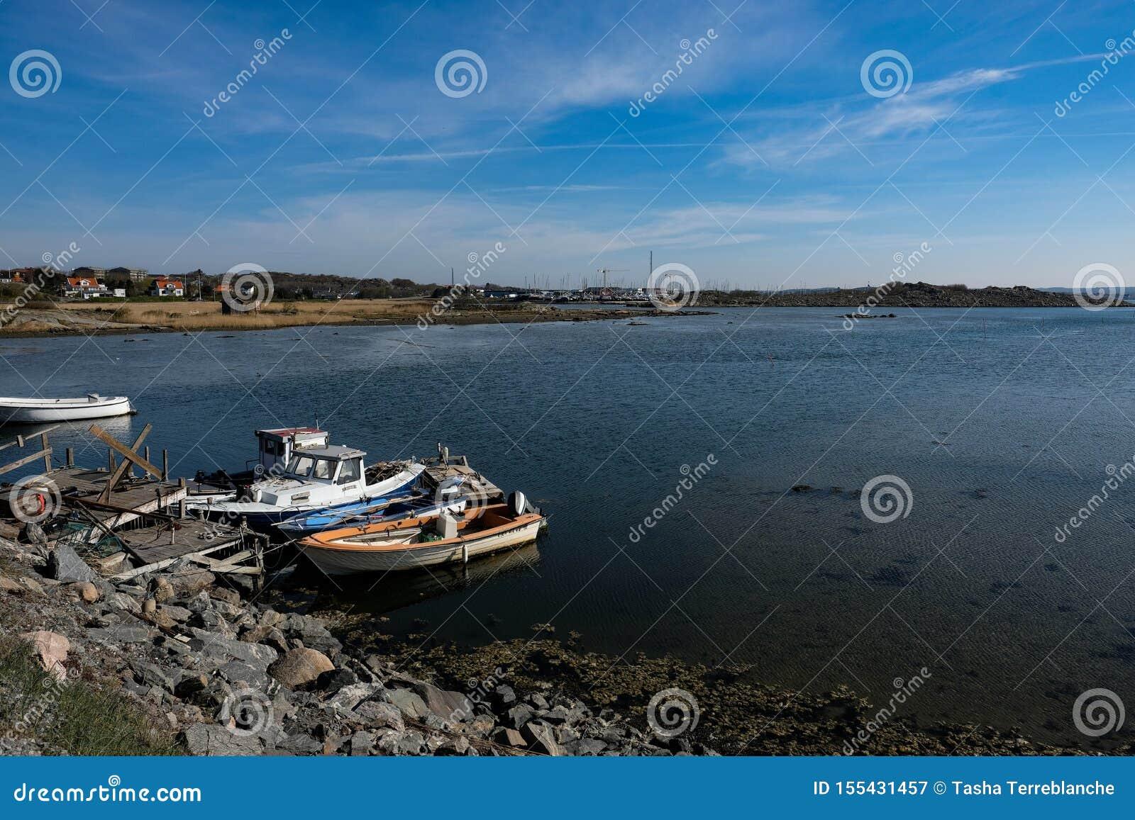 Barcos atracados en orilla rocosa