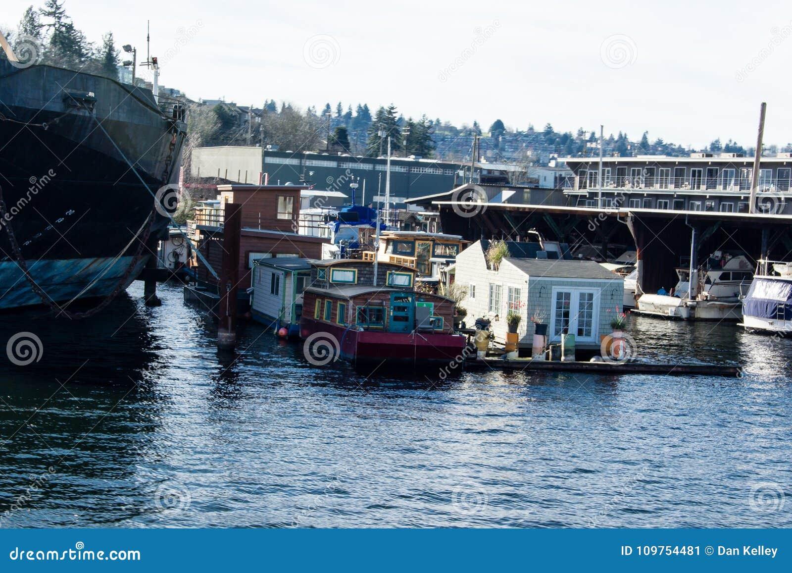 Barcos de casa em Salmon Bay transversalmente de Ballard ao lado de um navio