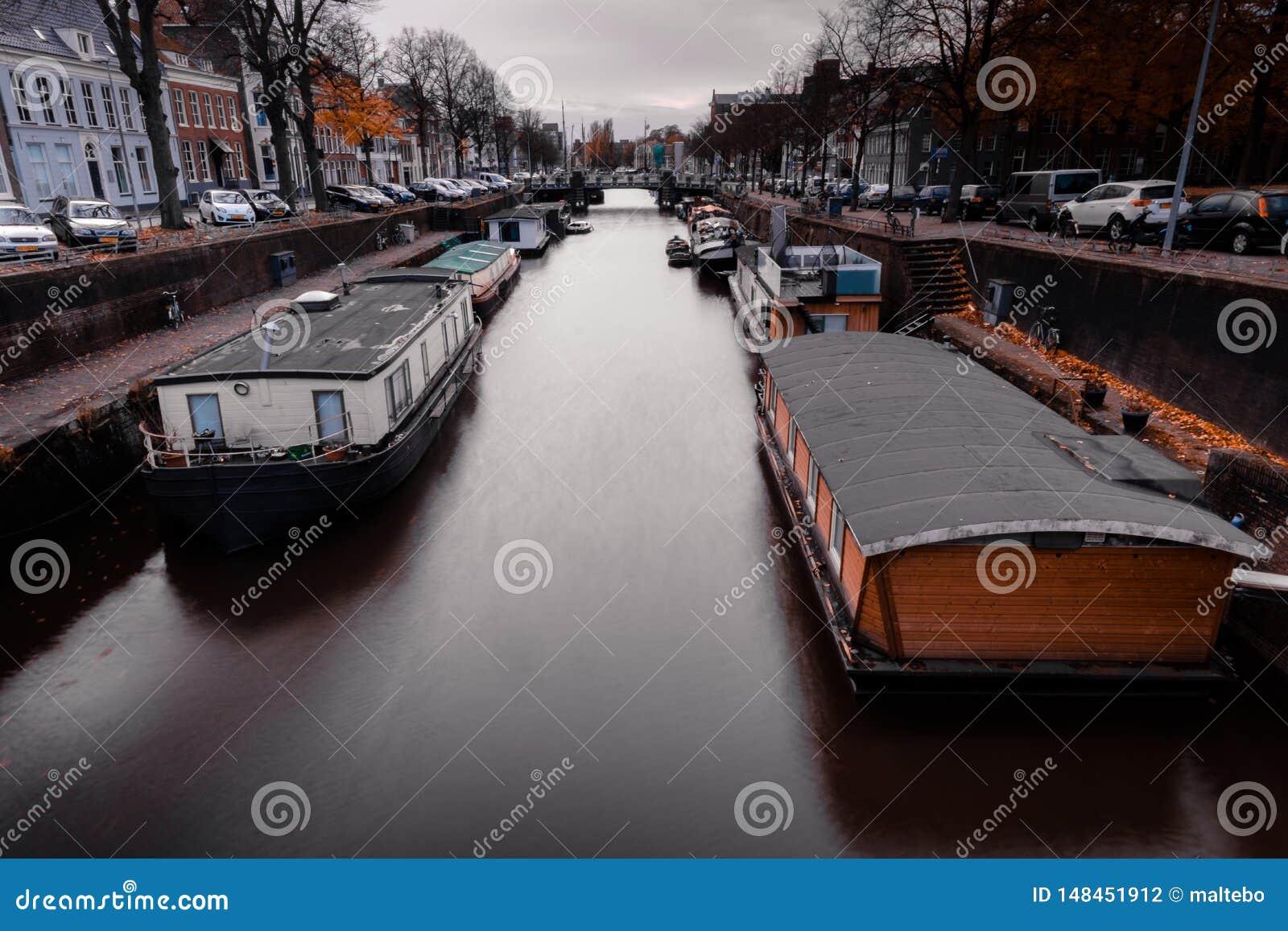 Barcos de casa em um canal nos Países Baixos