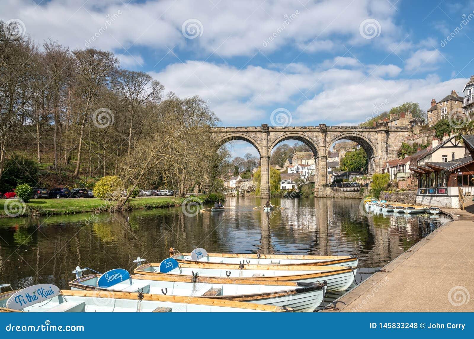 Barcos de enfileiramento para o aluguer em Knaresborough com rio Nidd e viaduto da estrada de ferro