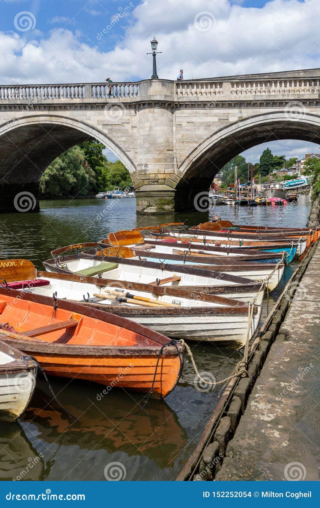 Barcos de madeira para o aluguer amarrados no rio Tamisa
