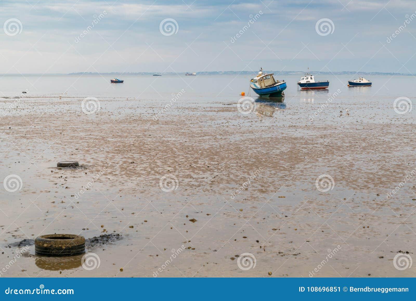 Barcos na maré baixa na costa do rio Tamisa