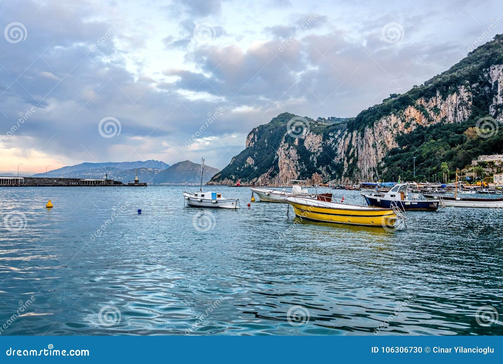 Barcos no porto principal da ilha de Capri sob céus nebulosos