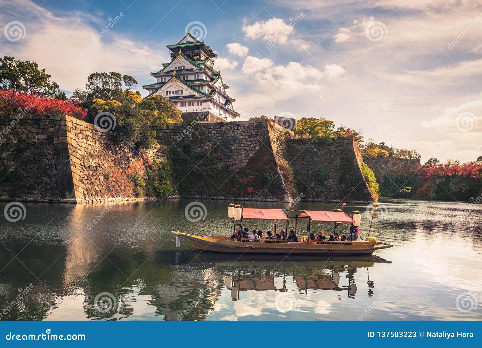 Barcos turísticos com os turistas ao longo do fosso de Osaka Castle, Osaka, Japão
