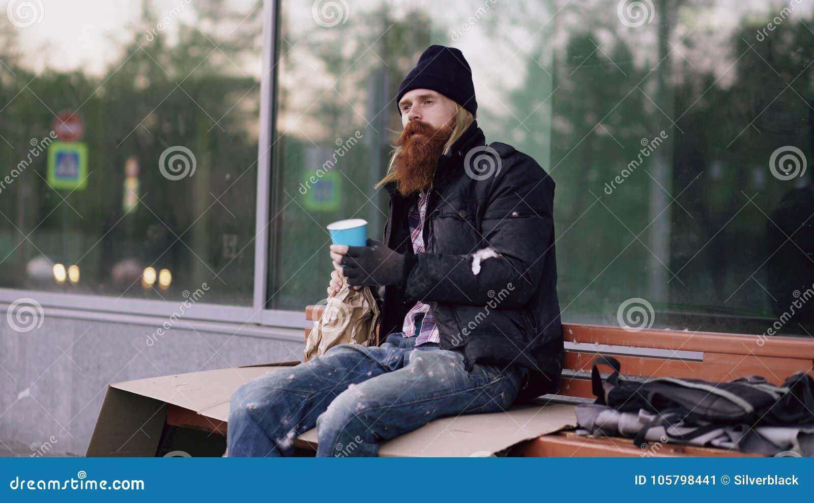 Bardzo pijący bezdomny mężczyzna opowiada zaludniać chodzący pobliskiego i błagać dla pieniądze on podczas gdy siedzący na ławce