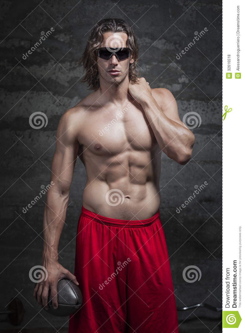 bare chested muscle man is holding football ball in hand