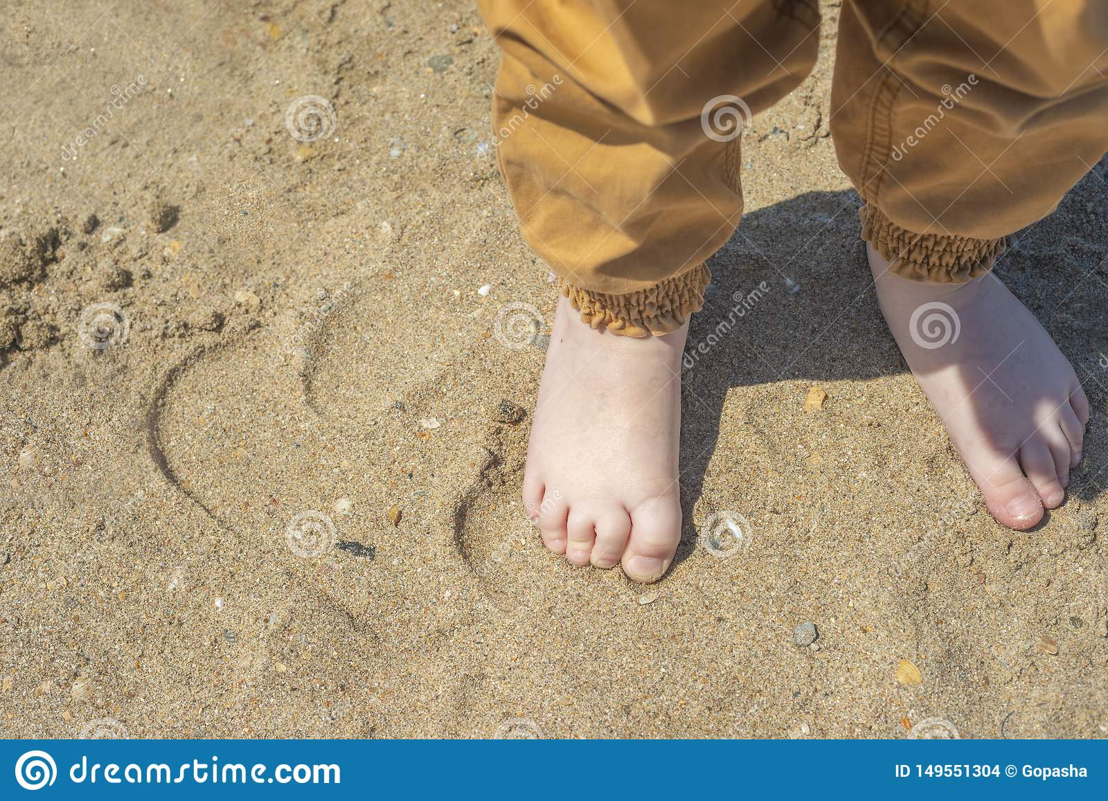 Bare children`s feet on the beach. close-up