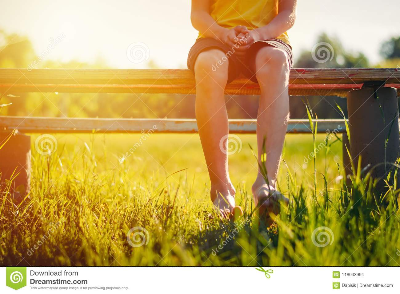 Bare feet of a boy hang down from a bench