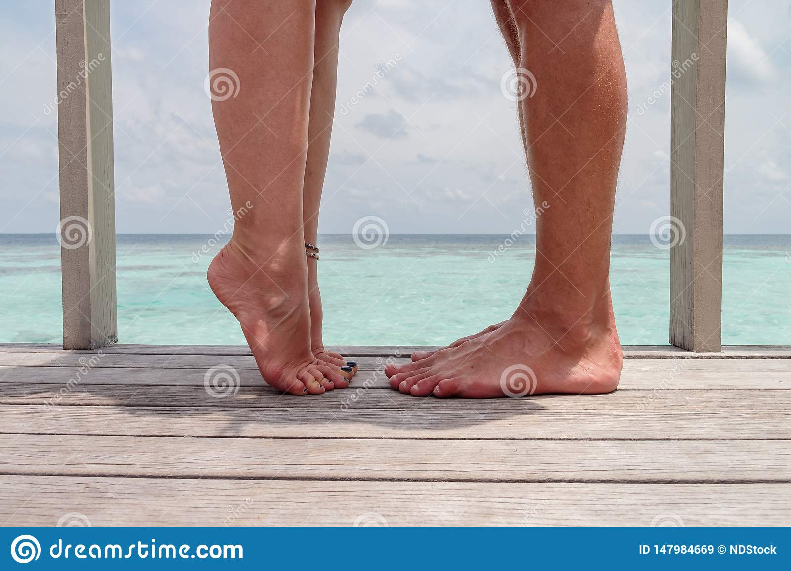 Closeup photo of woman and man legs, girl with raised leg. Couple kissing,  over sea background, he vs she