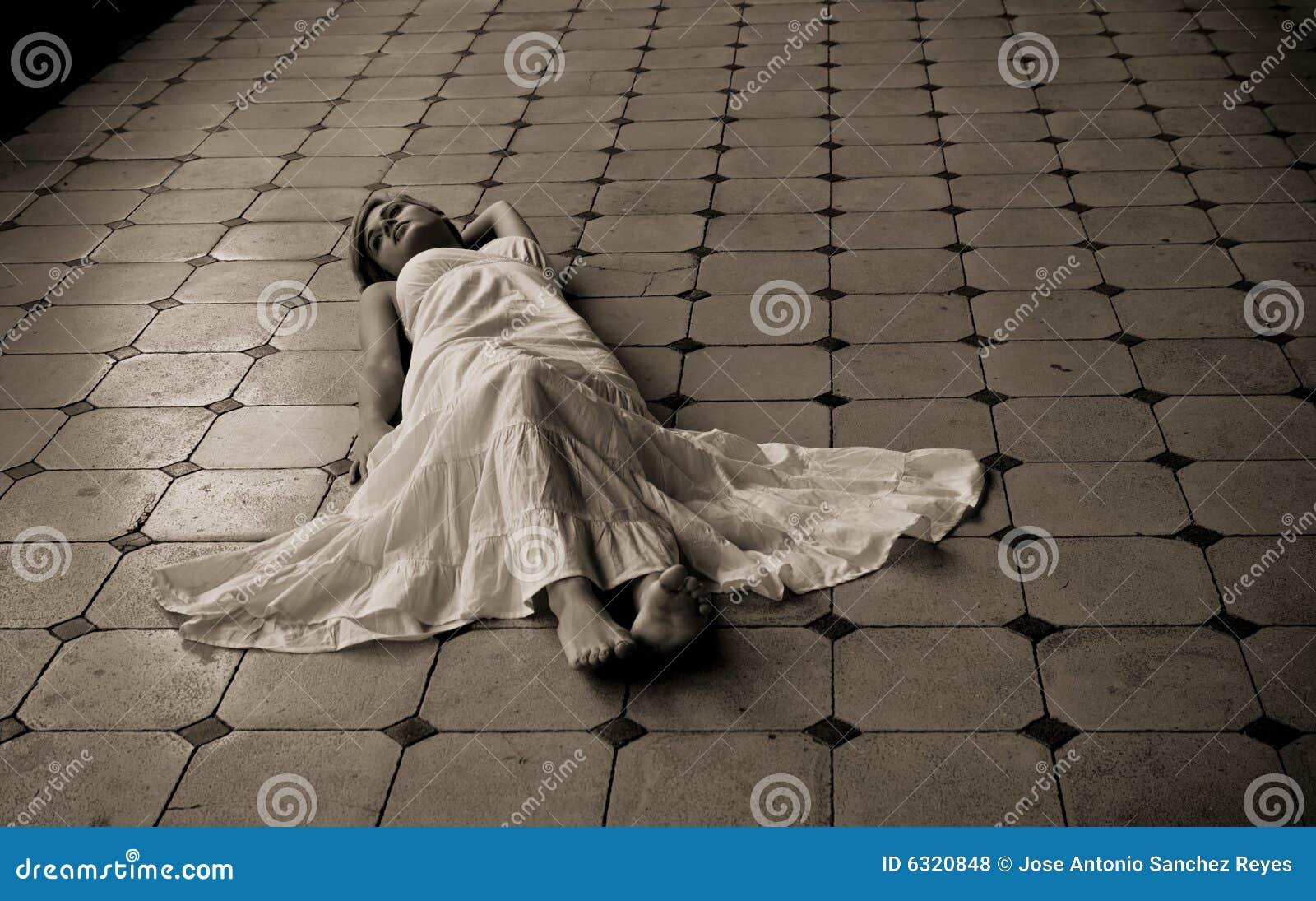 Barefeet πάτωμα που βάζει τη γυναί&