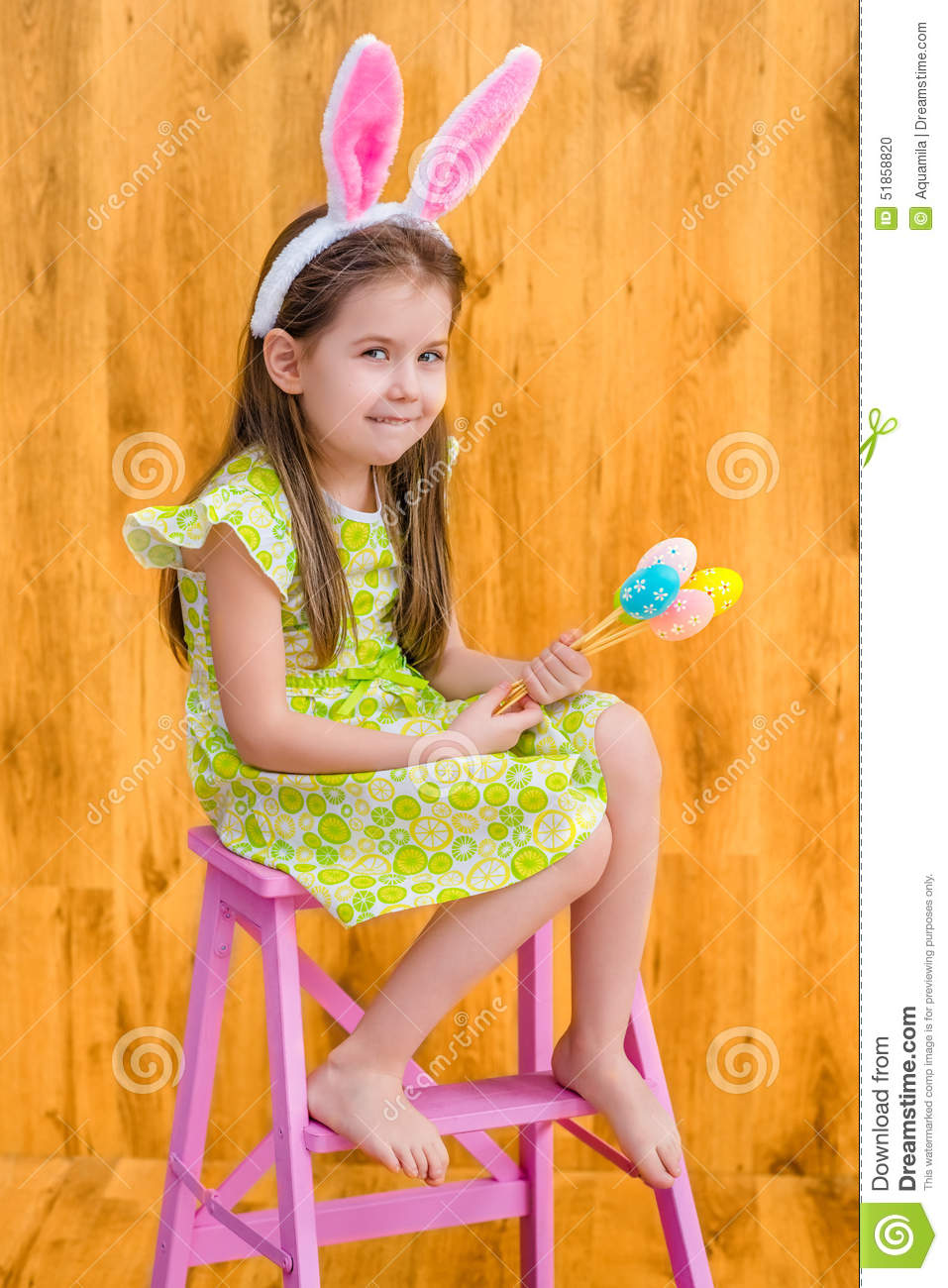 Barefooted girl wearing pink white rabbit or bunny ears and holding bunch of colorful eggs