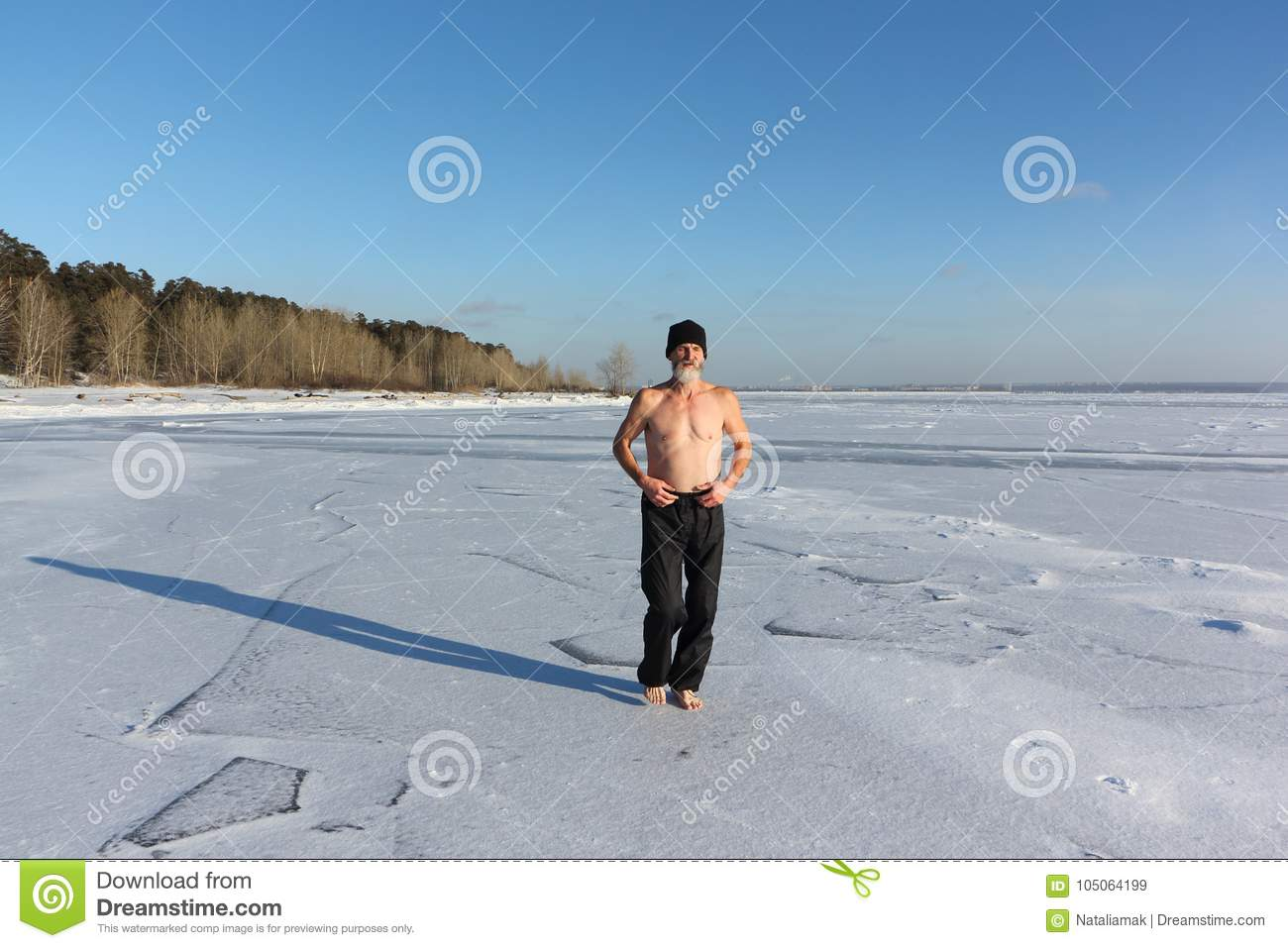 Barefooted man with a naked torso engaged cold conditioning on ice of a  frozen river , Ob Reservoir, Russia