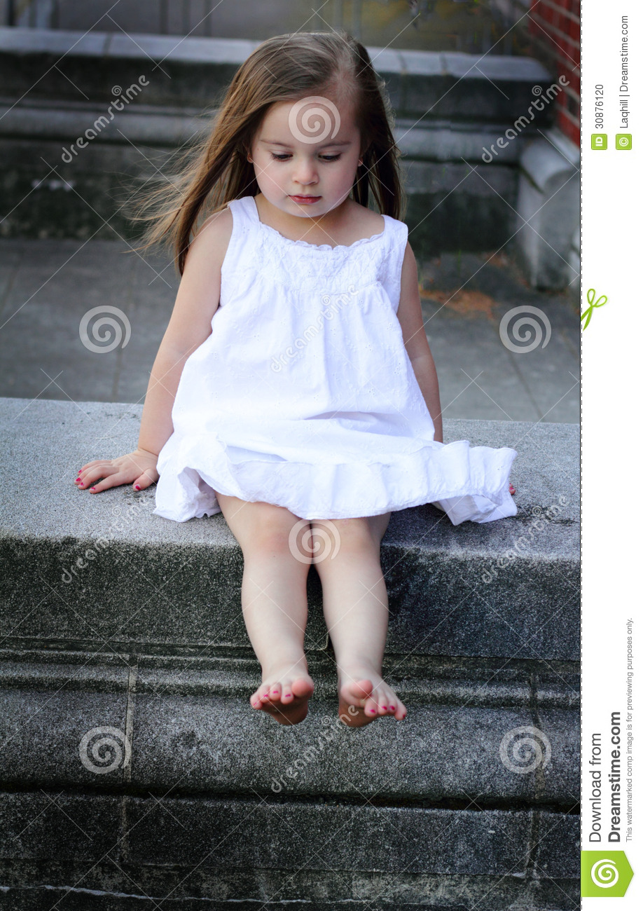 72376189794 A closeup of a barefooted little girl in a white summer dress sitting on a  concrete wall and looking down. Shallow depth of field.