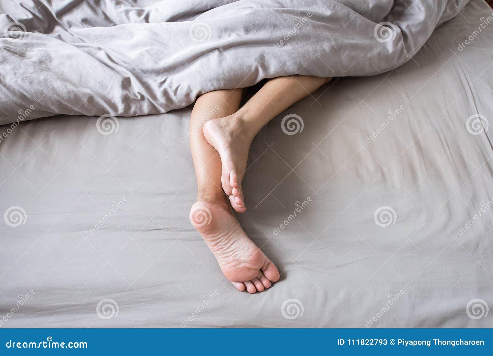 Barfuß und Bein unter Decke auf dem Bett nachdem dem Aufwachen am Morgen