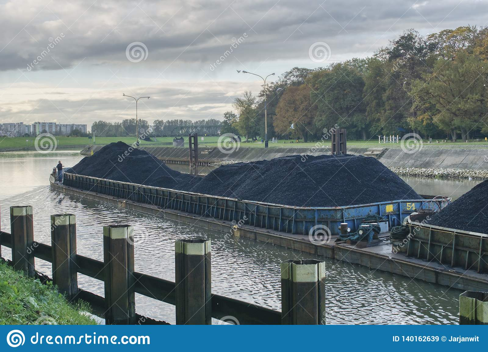 The barge flows along the river, transports coal to the power plant, repairing water routes, and green transport