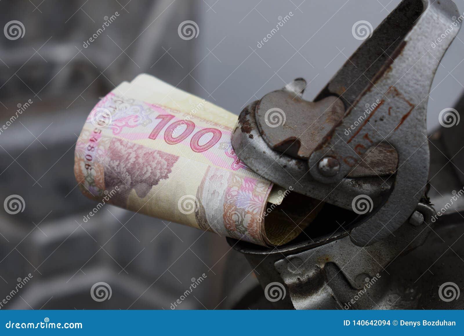 Barilotto del metallo e soldi ucraini, il concetto del costo di benzina, diesel, gas Riempimento dell automobile Rotolo delle ban