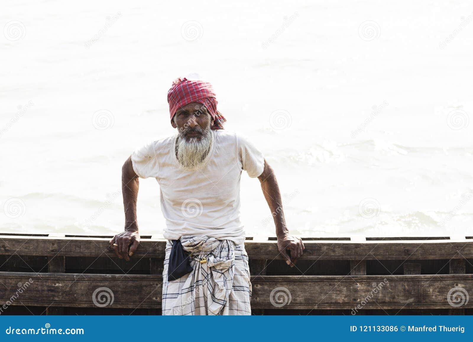 Barisal, Bangladesh, el 27 de febrero de 2017: Hombre mayor que presenta en el embarcadero