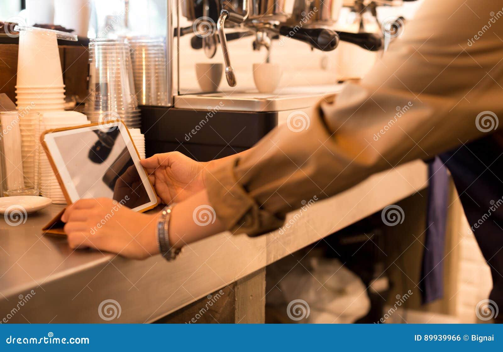Barista är handen genom att använda ipad med skjuten espresso i bakgrund