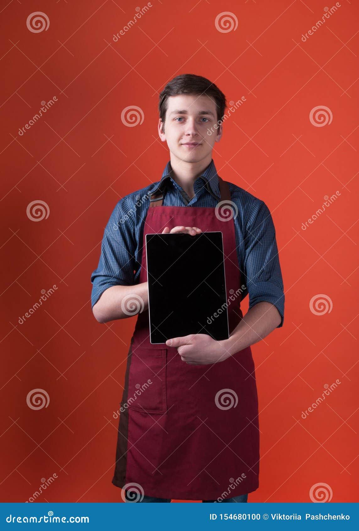 Barista με τη σκοτεινή τρίχα στο μπλε πουκάμισο και burgundy ποδιά που κρατά και που παρουσιάζει ψηφιακή ταμπλέτα με την κενή οθό