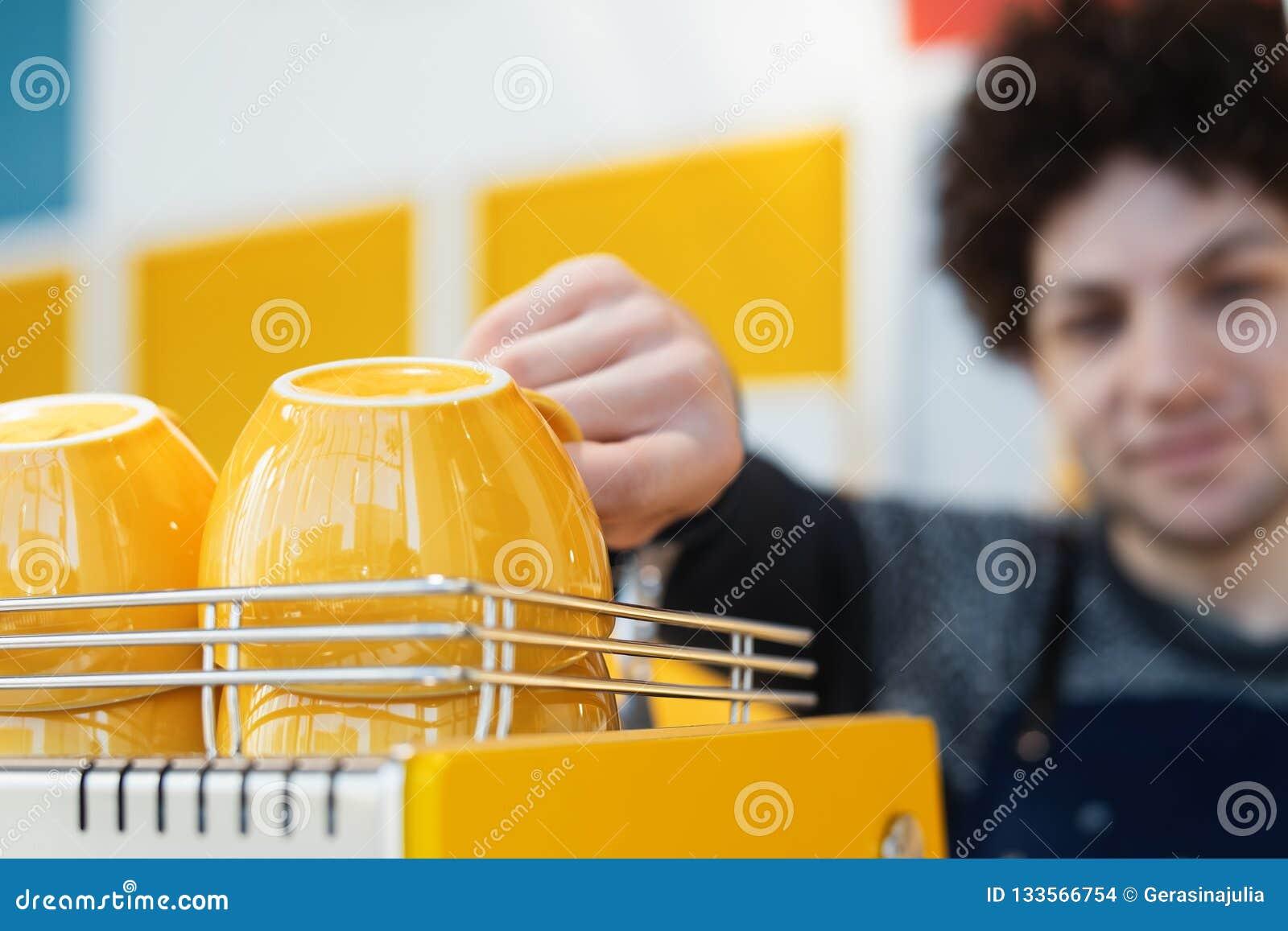 Barista amistoso que alcanza para la taza de café y que se coloca detrás de contador de la barra