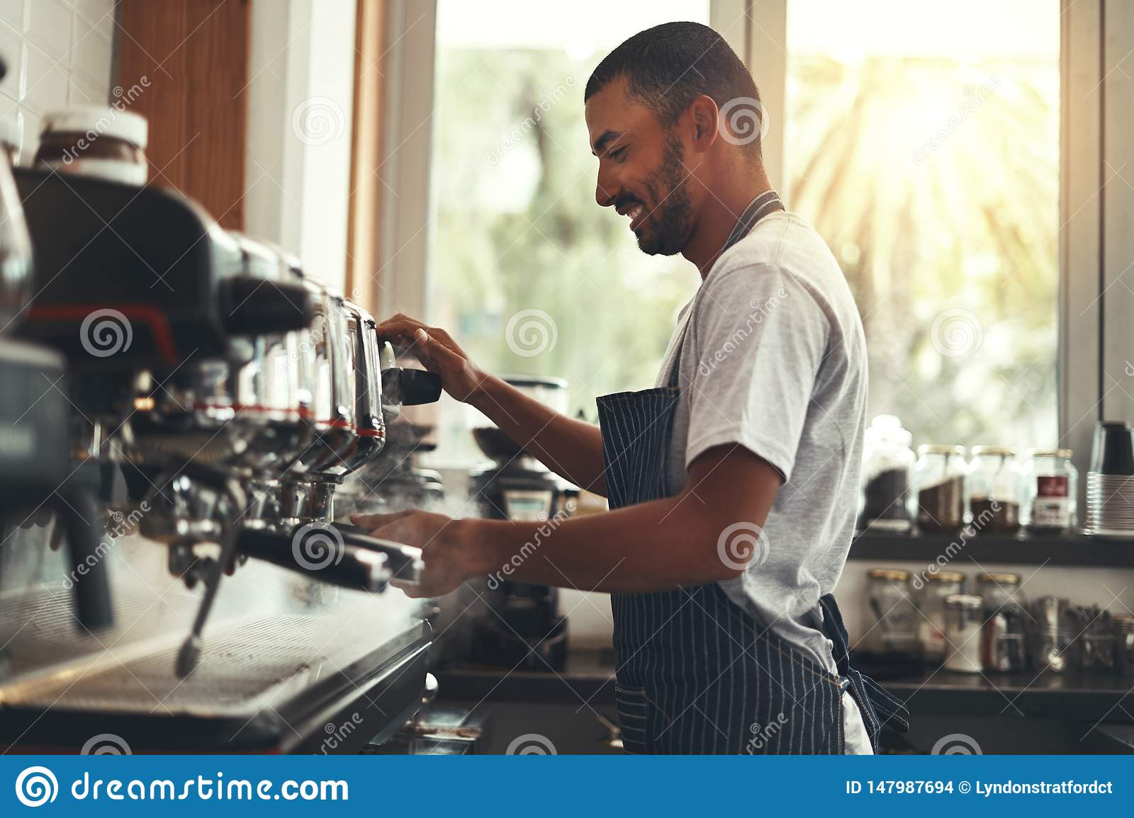 The barista makes cappuccino in cafe