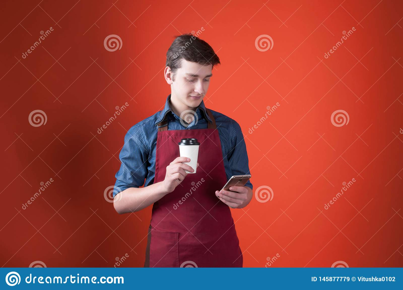 Barista con el pelo oscuro en el delantal de Borgoña que sostiene la taza de papel con café y que usa smartphone en fondo anaranj
