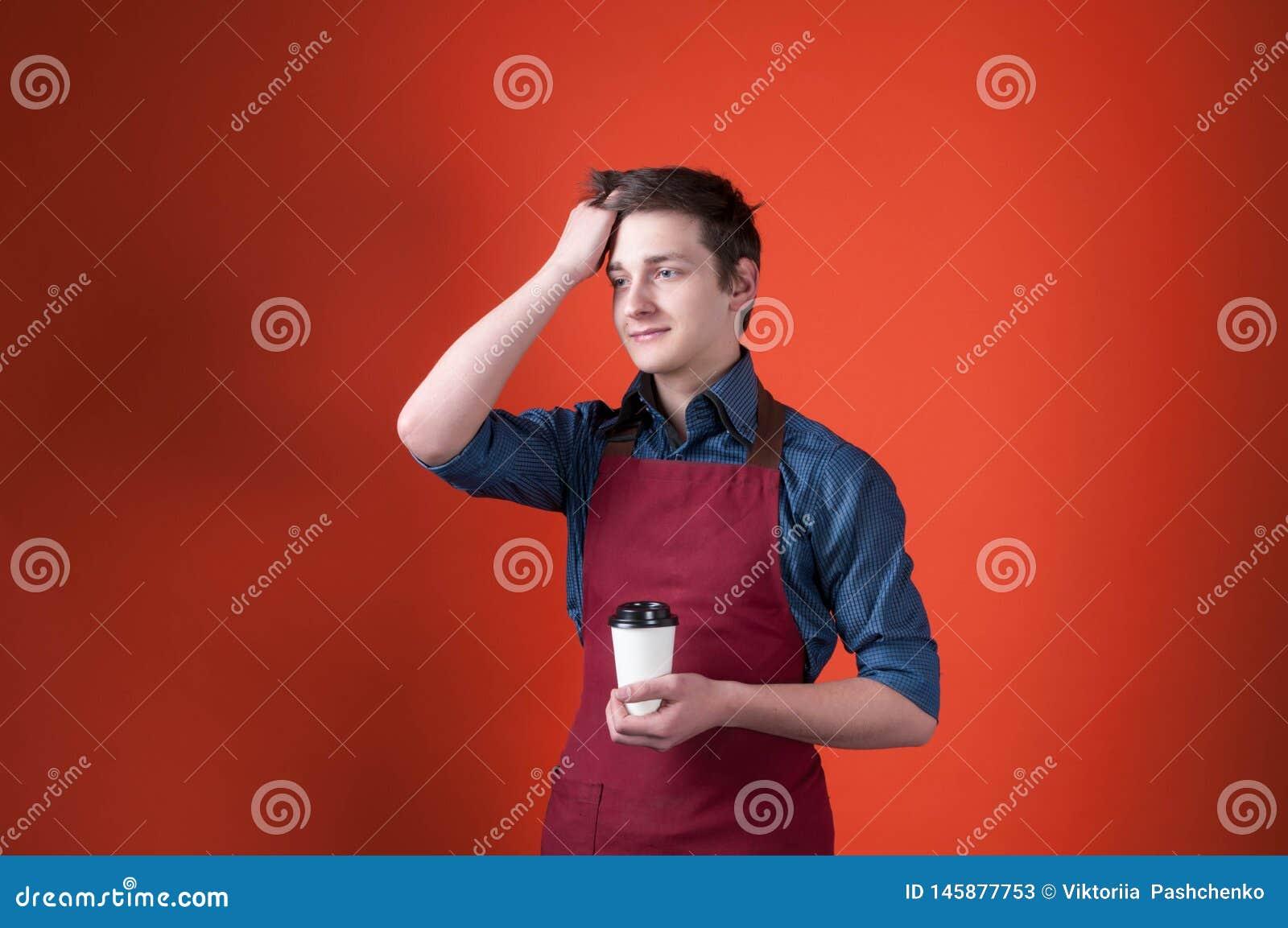 Barista con el pelo oscuro que mira lejos en el delantal de Borgoña, sosteniendo la taza de papel con café y corrigiendo el peina