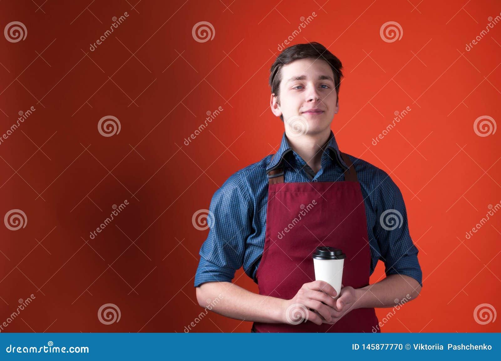 Barista decepcionado con la mueca en el delantal rojo que sostiene la taza de papel con café
