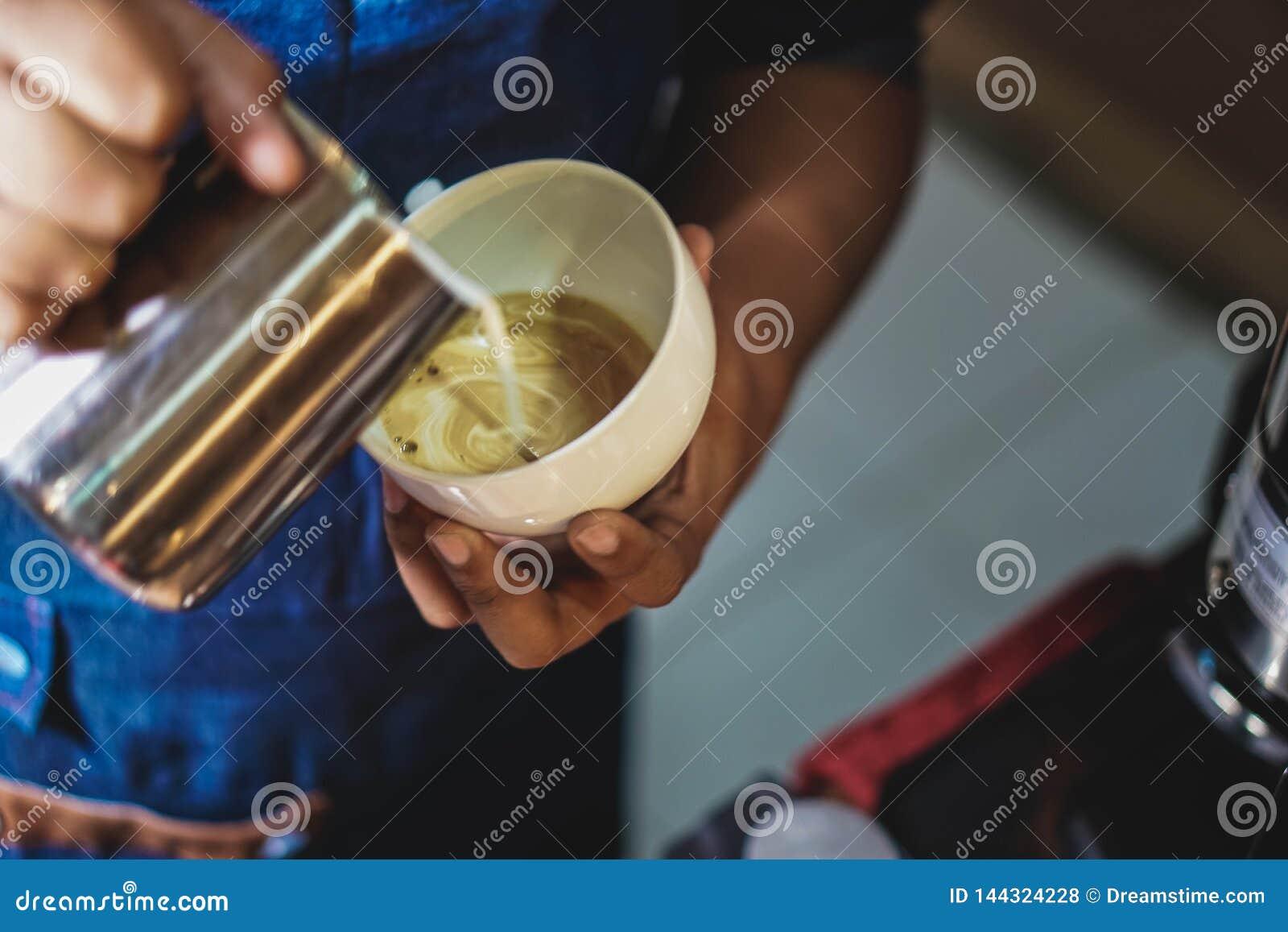 Barista dienende melk op een koffiekop